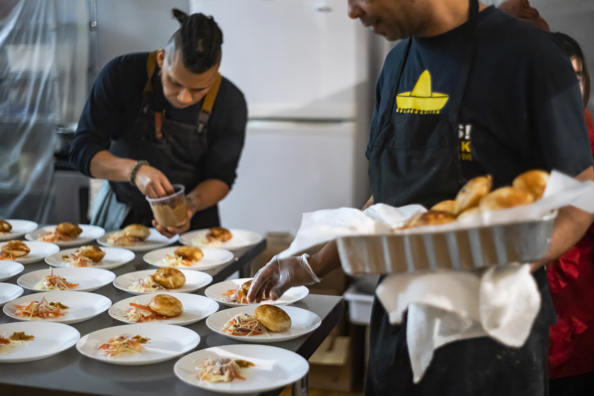 tow chefs in the kitchen plating delicious African cuisine